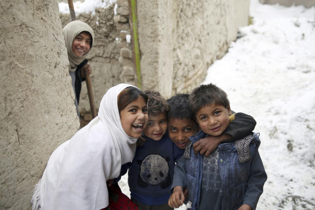 Internally displaced Afghan boys and girls pose for a photograph after a snowstorm at a camp on the outskirts of Kabul, Afghanistan, Sunday, Jan. 12, 2020. Kabul has been experiencing below freezing weather and snow. (AP Photo/Rahmat Gul)