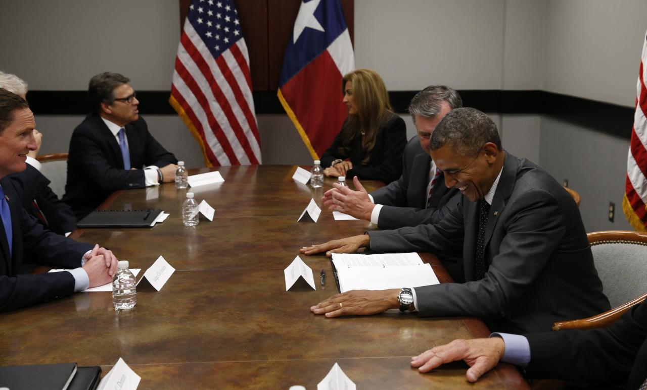 U.S. President Barack Obama (R) meets with Texas Governor Rick Perry (L, rear), local elected officials and faith leaders in Dallas, to discuss a surge of Latin American young people crossing the U.S.-Mexico border, July 9, 2014. Congressional Republicans on Wednesday cast a skeptical eye on a White House request for $3.7 billion to address an influx of child migrants at the U.S. border while Obama met with top critic Perry. REUTERS/Kevin Lamarque (UNITED STATES - Tags: POLITICS SOCIETY IMMIGRATION)