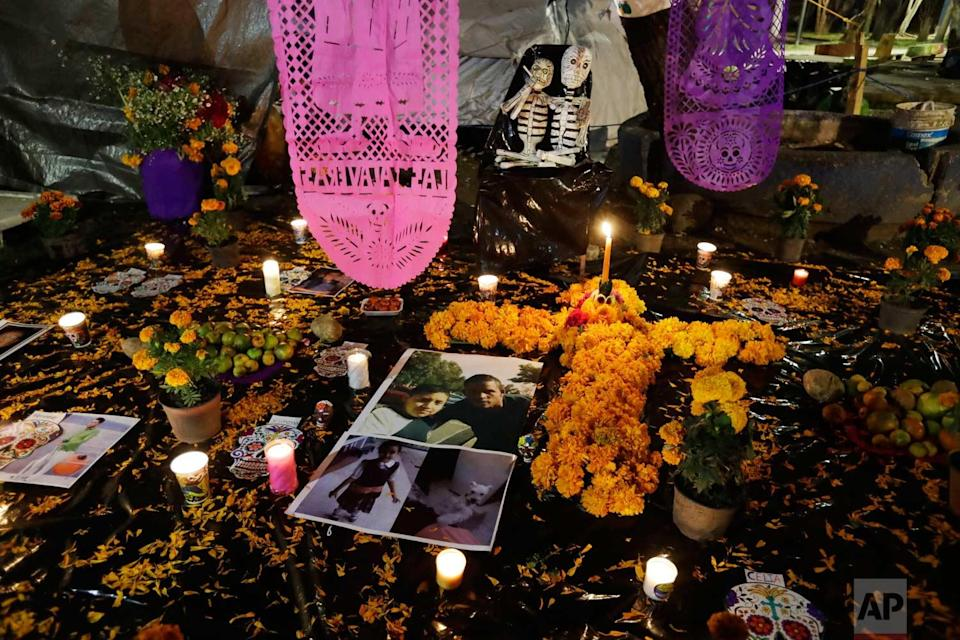 <p>Pictures of Julian Flores, 11, and his little sister Ximena, 6, lie amidst flowers and candles in a Day of the Dead altar erected in a tent camp outside Mulitfamiliar Tlalpan, where nine people including Nayeli Flores' two children were killed when a building collapsed in the Sept. 19 earthquake. (AP Photo/Rebecca Blackwell) </p>