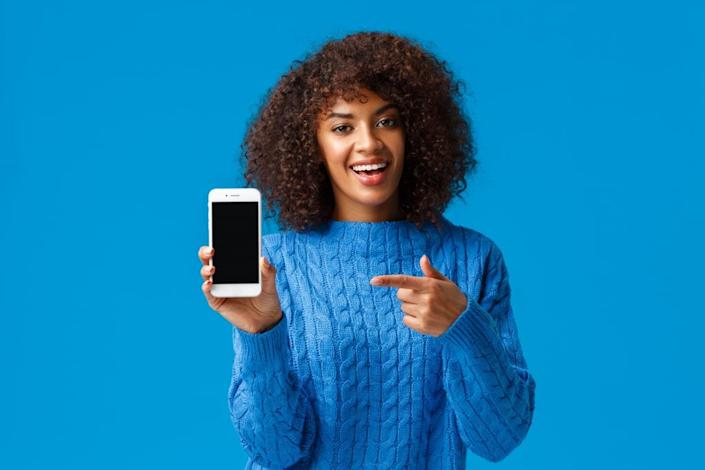 Check this out. Happy charismatic african-american woman with afro haircut, holding smartphone, showing mobile screen, pointing display as promote application, shopping app or game.