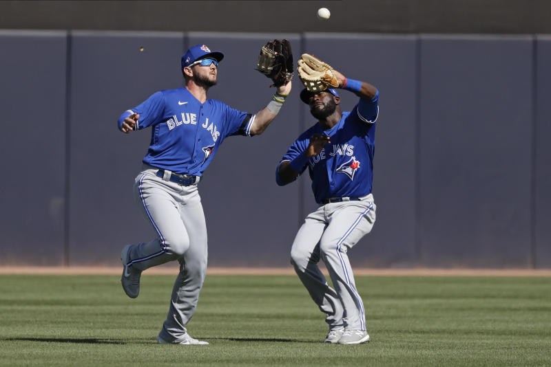 Toronto Blue Jays' Forest Wall, left, catches a ball hit by New York Yankees' Erik Kratz for an out while avoiding teammate Anthony Alford, right, during the fifth inning of a spring training baseball game Saturday, Feb. 22, 2020, in Tampa. (AP Photo/Frank Franklin II)