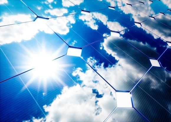 Solar panel reflecting the sun and blue skies with patchy clouds.