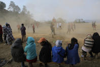 Spectators turn their faces from wind blowing dust after a friendly soccer match in Shangshak village, in the northeastern Indian state of Manipur, Saturday, Jan. 30 2021. The afternoon's match with a neighbouring village was arranged in a day's notice. Everyone who can play can get chosen for a match. Most from the host village had spent the hours before the match painting a house, a common practice in the community where the culture of helping hands remains deeply ingrained. (AP Photo/Yirmiyan Arthur)