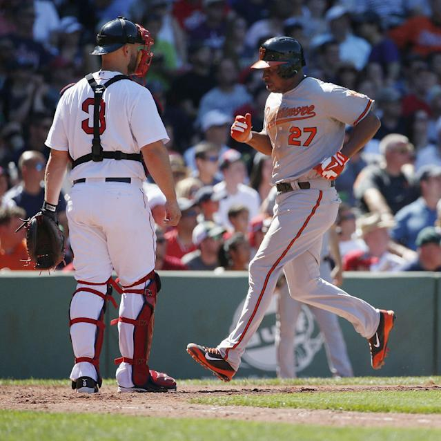 Baltimore Orioles' Delmon Young, right, scores in front of Boston Red Sox's David Ross, left, on a sacrifice fly by Caleb Joseph in the sixth inning of a baseball game in Boston, Sunday, July 6, 2014. (AP Photo/Michael Dwyer)