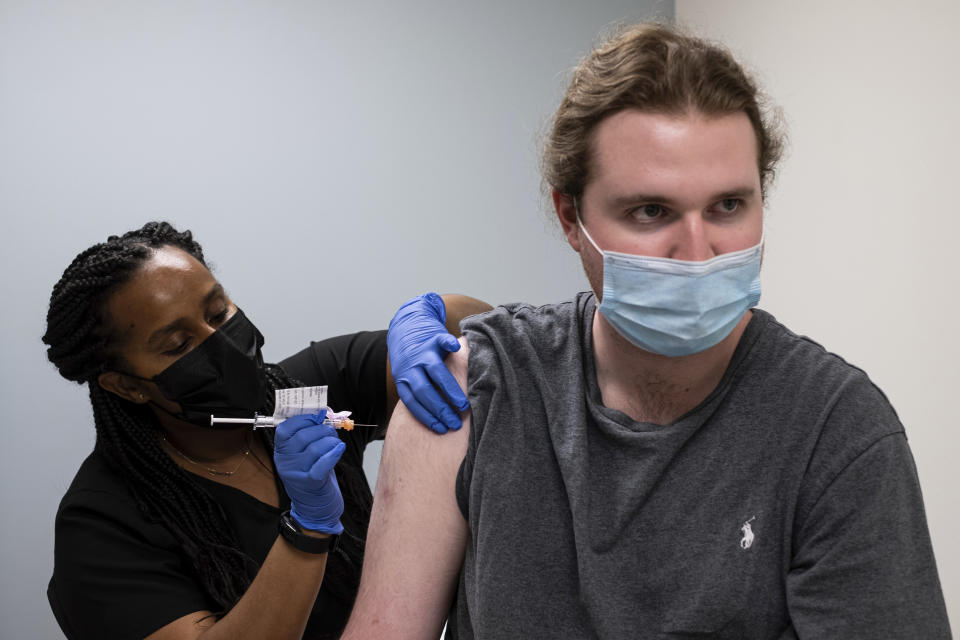 """Cole Smith receives a Moderna variant vaccine shot from clinical research nurse Tigisty Girmay at Emory University's Hope Clinic, on Wednesday afternoon, March 31, 2021, in Decatur, Ga. Smith, who received Moderna's original vaccine a year ago in a first-stage study, said returning wasn't a tough decision. """"The earlier one, it was a great success and, you know, millions of people are getting vaccinated now. ... If we're helping people with the old one, why not volunteer and help people with the new one?"""" (AP Photo/Ben Gray)"""