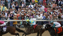 FILE - In this May 4, 2019, file photo, fans cheer as they watch a race at Churchill Downs before the 145th running of the Kentucky Derby horse race in Louisville, Ky. Next months Kentucky Derby will run without fans at Churchill Downs. The historic track cited rises in COVID-19 cases in the Louisville area. (AP Photo/John Minchillo, File)
