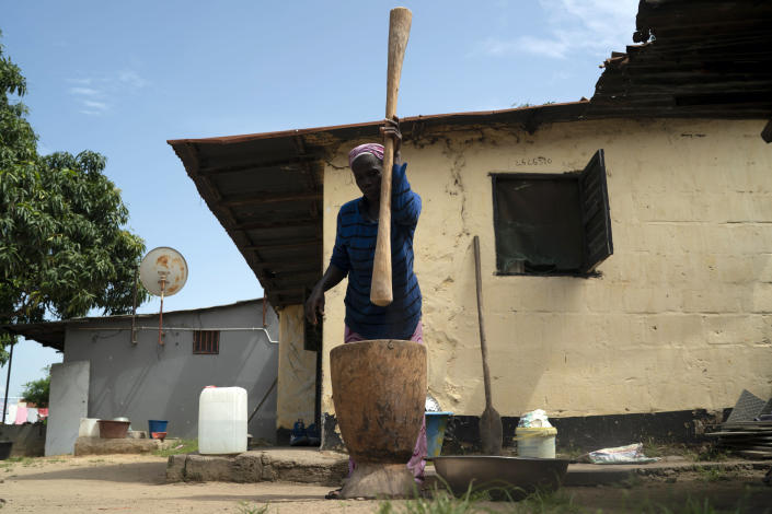 """Lucy Jarju pounds rice in a mortar with a pestle at her home in Serrekunda, Gambia, Sunday, Oct. 3, 2021. Jarju, 53, says she isn't willing to be vaccinated against COVID-19 if it means she could miss even a day's work. """"If my arm gets heavy and I can't go to the water, who will feed my children?"""" Her husband died a decade ago, leaving her alone to provide for her seven children. (AP Photo/Leo Correa)"""