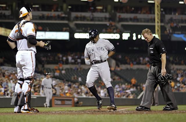 New York Yankees' Curtis Granderson, center, crosses home plate between Baltimore Orioles catcher Matt Wieters, left, and home plate umpire Jim Wolf after hitting a solo home run in the seventh inning of a baseball game, Thursday, Sept. 12, 2013, in Baltimore. (AP Photo/Patrick Semansky)
