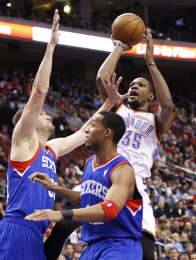 Oklahoma City Thunder's Kevin Durant, right, shoots as Philadelphia 76ers' Spencer Hawes, left, and Evan Turner defend during the first half of an NBA basketball game, Saturday, Jan. 25, 2014, in Philadelphia. (AP Photo/Chris Szagola)