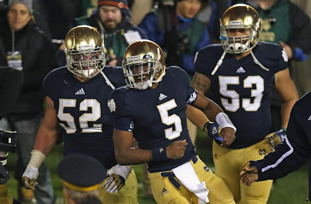 SOUTH BEND, IN - NOVEMBER 03: Everett Golson #5, Braxston Cave #52 and Justin Utupo #53 of the Notre Dame Fighting Irish celebrate after Golson ran for the game-winning touchdown against the Pittsburgh Panthers at Notre Dame Stadium on November 3, 2012 in South Bend, Indiana. Notre Dame defeated Pittsburgh 29-26 in triple overtime. (Photo by Jonathan Daniel/Getty Images)