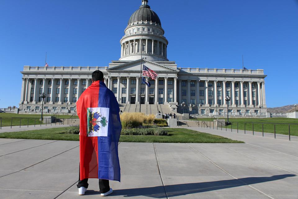 A supporter of Haitian immigrant rights draped in the Caribbean country's flag stands in front of the Utah Capitol on Friday, Sept. 24. (Enrique Limón)
