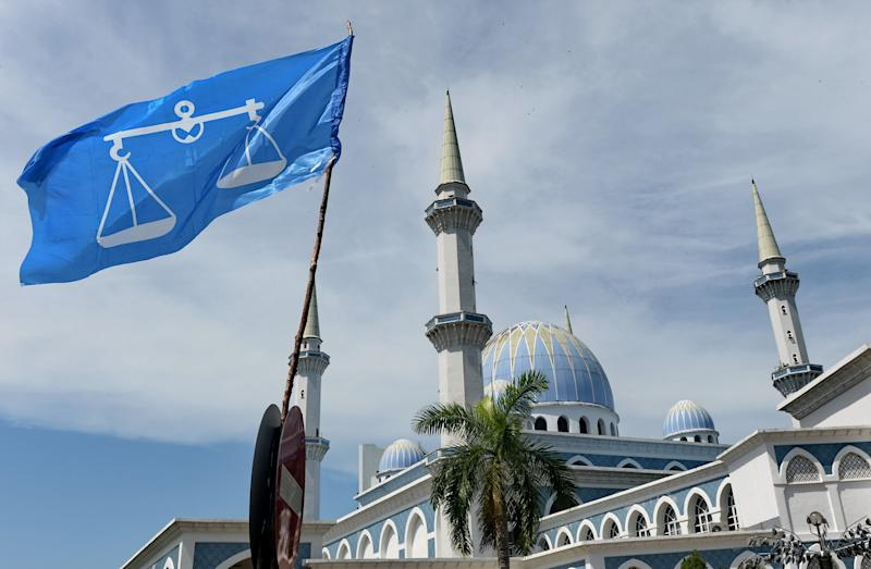 The Barisan National party flag (L) flies next to the Sultan Ahmad Shah State Mosque in Kuantan, the home-town of former Malaysia's Prime Minister Najib Razak. (Photo: ROSLAN RAHMAN/AFP via Getty Images)