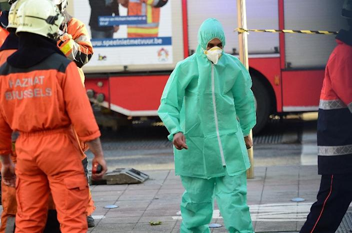 A person dressed in a protective suit is evacuated from Brussels Great Mosque and led to an ambulance, on November 26, 2015 (AFP Photo/Emmanuel Dunand)