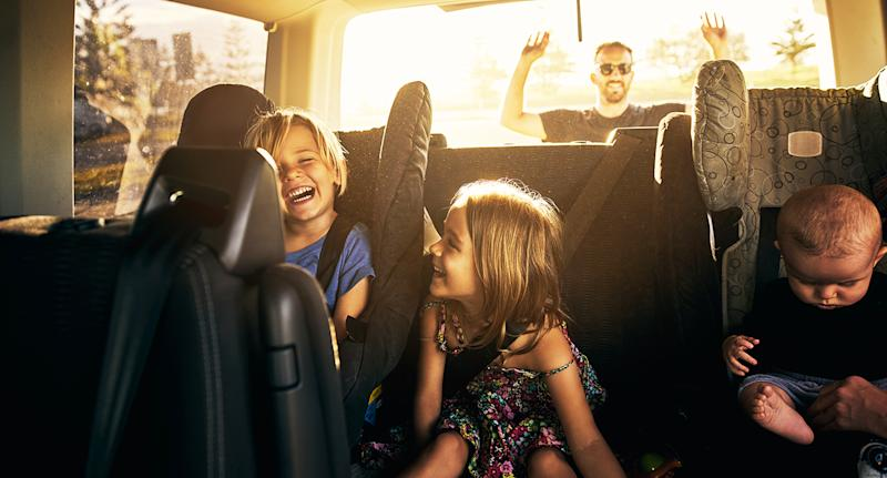 Shot of adorable little children sitting in a car and a dad closing the boot.