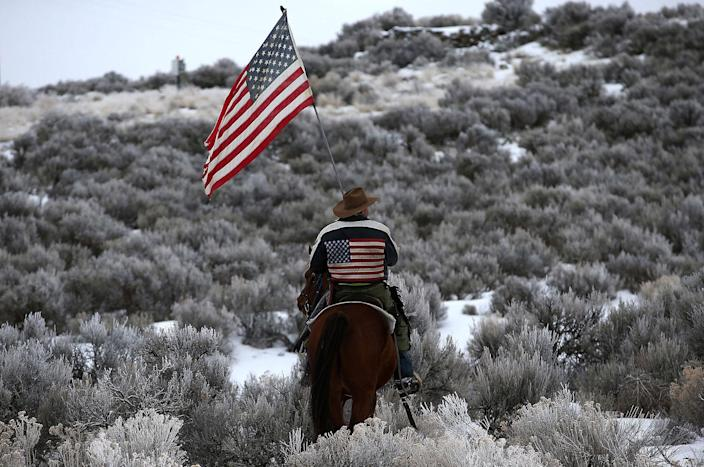 <p>JAN. 7, 2016 — Dwayne Ehmer carries an American flag as he rides his horse on the Malheur National Wildlife Refuge near Burns, Oregon. An armed anti-government militia group continues to occupy the Malheur National Wildlife Headquarters as they protest the jailing of two ranchers for arson. (Justin Sullivan/Getty Images) </p>