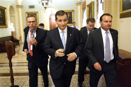 Cruz and Lee depart the Senate floor after their speeches before the night-time budget vote at the U.S. Capitol in Washington