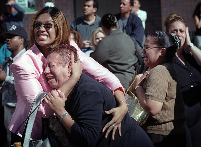 Two women hold each other as they watch the World Trade Center burn in New York Tuesday, Sept. 11, 2001. (AP Photo/Ernesto Mora)