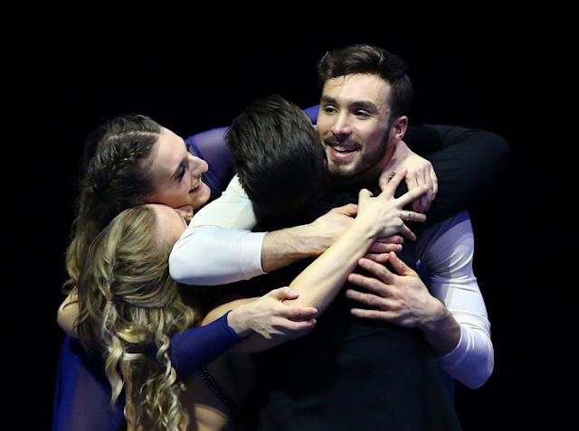 Figure Skating - World Figure Skating Championships - The Mediolanum Forum, Milan, Italy - March 24, 2018 France's Gabriella Papadakis and Guillaume Cizeron on the podium after winning the gold medal in the Ice Dance Free Dance hug second placed Madison Hubbell and Zachary Donohue of the U.S. REUTERS/Alessandro Bianchi