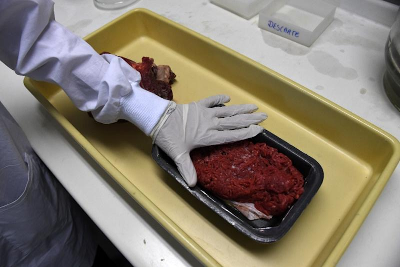 Experts get ready for analyzing animal meat seized in different markets in Rio de Janeiro, Brazil, on March 20, 2017, following a police investigation reporting allegations that corrupt exporters sold tainted products (AFP Photo/VANDERLEI ALMEIDA)