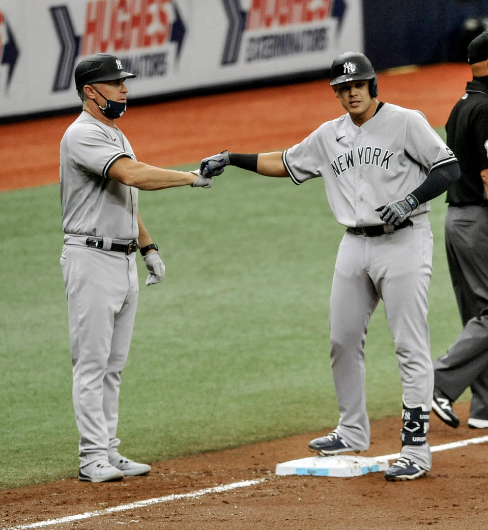 New York Yankees third base coach Phil Nevin, left, congratulates Gio Urshela, right, after two runs scored on an error by Tampa Bay Rays center fielder Manuel Margot during the fifth inning of a baseball game Sunday, Aug. 9, 2020, in St. Petersburg, Fla. (AP Photo/Steve Nesius)