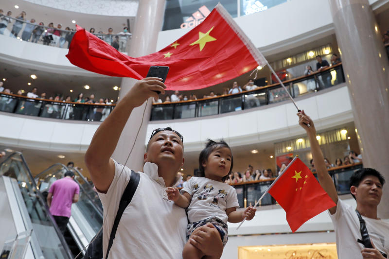 Pro-China supporters wave Chinese national flag in a shopping mall in Hong Kong, Wednesday, Sept. 18, 2019. Activists involved in the pro-democracy protests in Hong Kong appealed to U.S. lawmakers Tuesday to support their fight by banning the export of American police equipment that is used against demonstrators and by more closely monitoring Chinese efforts to undermine civil liberties in the city. (AP Photo/Kin Cheung)