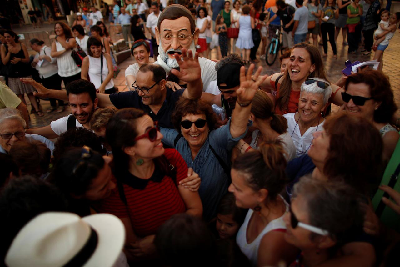 People and an activist of global anti-poverty charity Oxfam, wearing a mask depicting Spanish Prime Minister Mariano Rajoy, react as they take part in a protest as part of a campaign to denounce the non-fulfillment of the Spanish government's commitments to welcome refugees, in downtown Malaga, southern Spain June 20, 2017. REUTERS/Jon Nazca