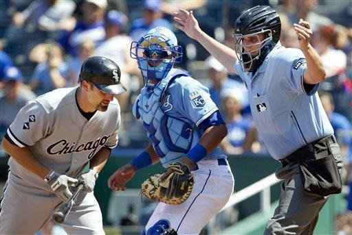 Home plate umpire Jordan Baker, right, calls a timeout after Chicago White Sox's Paul Konerko (14) gets hit by a pitch during the eighth inning of a baseball game at Kauffman Stadium in Kansas City, Mo., Sunday, July 15, 2012. Kansas City Royals catcher Salvador Perez watches. (AP Photo/Orlin Wagner)