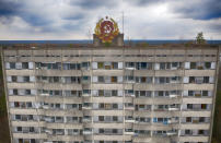 The rusty emblem of the Soviet Union is seen on the roof of an apartment building in the ghost town of Pripyat close to the Chernobyl nuclear plant, Ukraine, Thursday, April 15, 2021. The vast and empty Chernobyl Exclusion Zone around the site of the world's worst nuclear accident is a baleful monument to human mistakes. Yet 35 years after a power plant reactor exploded, Ukrainians also look to it for inspiration, solace and income. (AP Photo/Efrem Lukatsky)