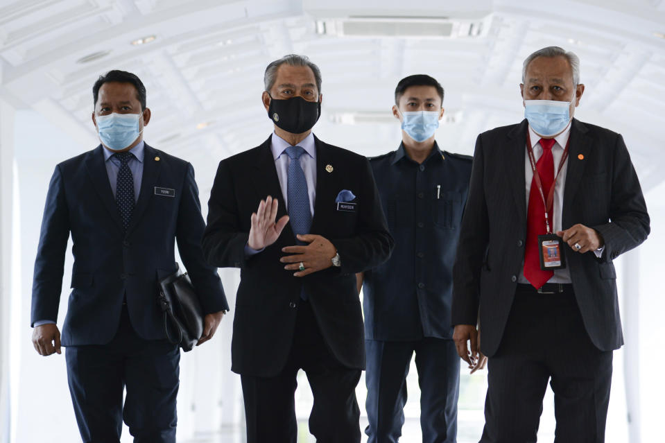 In this photo release by Malaysia Information Ministry, Malaysia's Prime Minister Muhyiddin Yassin, second left, waves as he arrives for a session of the lower house of parliament, in Kuala Lumpur, Malaysia Thursday, Nov. 26, 2020. Malaysia's Parliament Thursday approved the government's proposed 2021 budget, throwing a political lifeline to embattled Prime Minister Muhyiddin Yassin amid strong resistance to his nine-month-old leadership. (Famer Roheni/Malaysia's Department of Information via AP)
