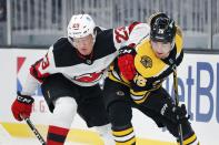New Jersey Devils' Mikhail Maltsev (23) and Boston Bruins' Connor Clifton (75) battle for the puck during the first period of an NHL hockey game, Sunday, March 7, 2021, in Boston. (AP Photo/Michael Dwyer)