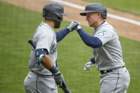 Seattle Mariners' Kyle Seager, right, celebrates with Jose Marmolejos, left, his solo home run against the Minnesota Twins in the sixth inning of a baseball game Sunday, April 11, 2021, in Minneapolis. (AP Photo/Bruce Kluckhohn)