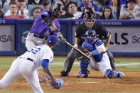 Colorado Rockies' Sam Hilliard, left, hits a solo home run as Los Angeles Dodgers relief pitcher Darien Nunez, left, watches along with catcher Will Smith, right, and home plate umpire Ed Hickox during the ninth inning of a baseball game Friday, July 23, 2021, in Los Angeles. (AP Photo/Mark J. Terrill)