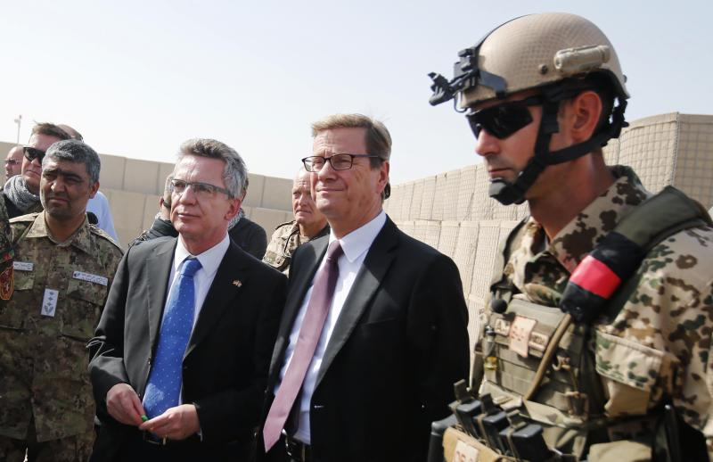 German Defence Minister Thomas de Maiziere, center left, and German Foreign Minister Guido Westerwelle, center right, arrive for the handover ceremony of a German base to the Afghan armed forces in Kunduz, Afghanistan, Sunday, Oct. 6, 2013. Soldiers of the German contingency of the International Security Assistance Force, ISAF, withdrew from their base in Kunduz and the camp will be used by the Afghan National Army, ANA, and the Afghan National Civil Order Police, ANCOP. (AP Photo/Fabrizio Bensch, Pool)