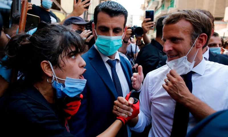 Emmanuel Macron listens to a resident on a street in Beirut on Thursday.