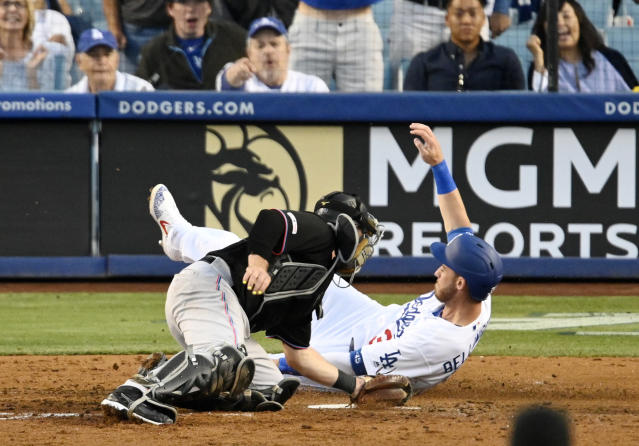 Los Angeles Dodgers' Cody Bellinger, right, scores ahead of the tag of Miami Marlins catcher Bryan Holaday on a double by Max Muncy during the fifth inning of a baseball game Saturday, July 20, 2019, in Los Angeles. (AP Photo/Mark J. Terrill)