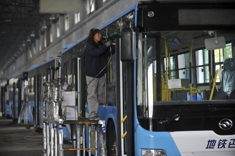 In this photo taken Saturday Oct. 20, 2012, a female worker labors on a assembly line at a bus manufacturer in Dandong city in northeast China's Liaoning province.  China's manufacturing improved this month, adding to signs an economic recovery might be taking shape after a sharp slump in the world's No. 2 economy. (AP Photo) CHINA OUT