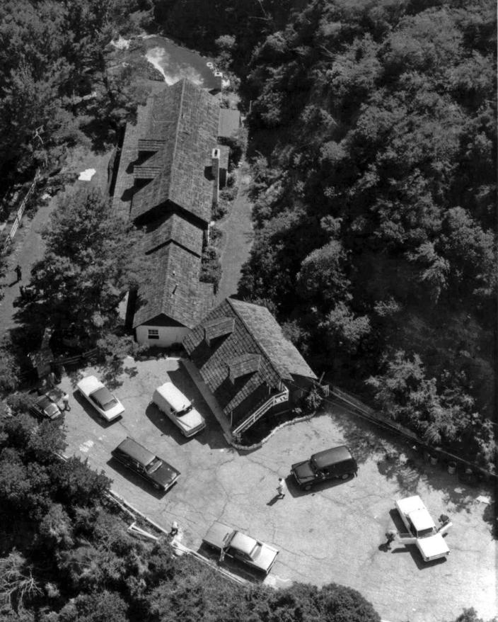 FILE - This Aug. 9, 1969 file photo shows the home of actress Sharon Tate and director Roman Polanski, after Tate and four others were murdered Aug. 8-9, 1969. One body is under a sheet at upper left; another is in the car at lower right. Fifty years ago Charles Manson dispatched a group of disaffected young followers on a two-night killing rampage that terrorized Los Angeles and, in the years since, has come to represent the face of evil. (AP Photo/File)