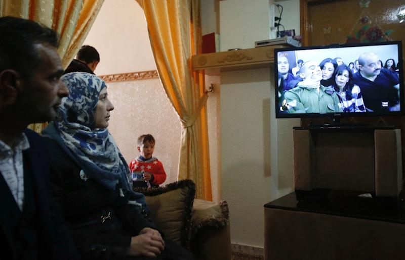 The Palestinian parents of Abdul Fatah al-Sharif -- who was shot dead as he lay on the ground by Israeli soldier Elor Azaria in March 2016 -- watch the soldier's televised trial, at their family home in Hebron, on February 21, 2017 (AFP Photo/HAZEM BADER)