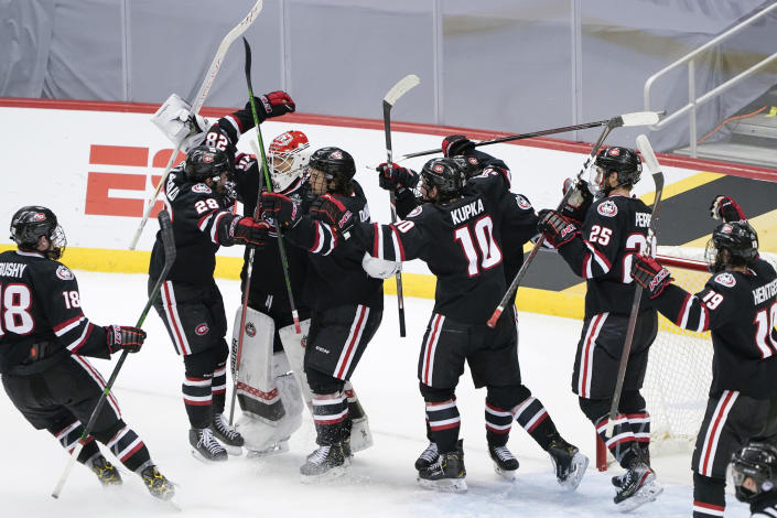 St. Cloud State goaltender David Hrenak, third from left, celebrates with teammates after a 5-4 win over Minnesota State in an NCAA men's Frozen Four hockey semifinal in Pittsburgh, Thursday, April 8, 2021. (AP Photo/Keith Srakocic)