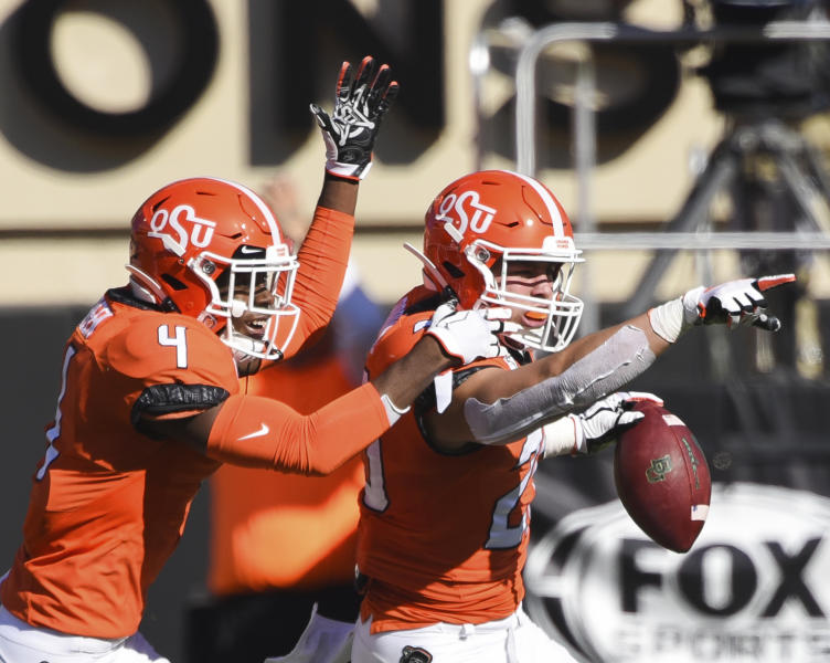 Oklahoma State corner back Tanner McCalister (4) and linebacker Malcolm Rodriguez (20) celebrate after Rodriguez recovered a Baylor fumble he forced during the first quarter of an NCAA college football game in Stillwater, Okla., Saturday, Oct. 19, 2019. (AP Photo/Brody Schmidt)