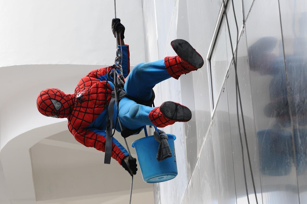 SURABAYA, INDONESIA - JULY 12: Indonesian 'Spider-Man' window cleaner, 37-year-old Teguh is seen lowering himself to the ground after cleaning the glass windows of the 18-storey Alana Hotel on July 12, 2013 in Surabaya, Indonesia. Teguh is a specialist glass window cleaner working on high-rise buildings wearing a Spider-Man uniform and working at an altitude of over 500 meters above ground level. He earns between Rp. 5 million and 15 million depending on the height of the building and the level of difficulty. (Photo by Robertus Pudyanto/Getty Images)