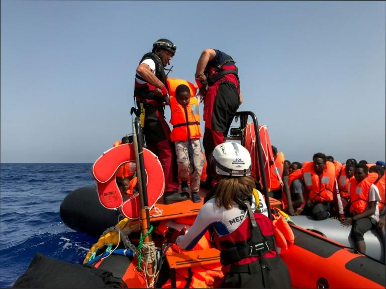 Crew members of the Ocean Viking rescue ship are shown here helping a child board their dinghy