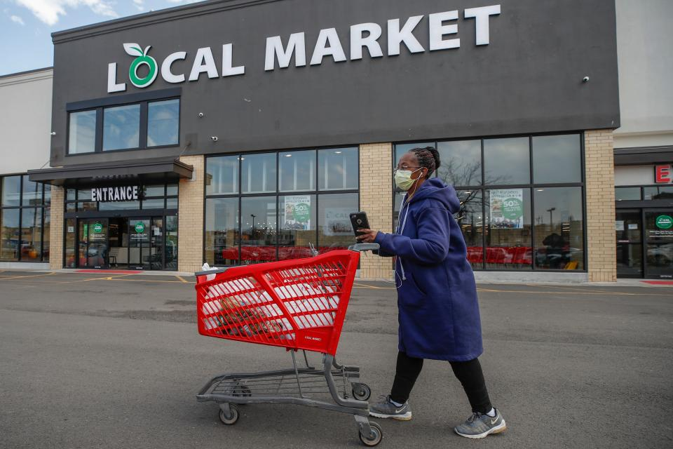 A woman leaves the Local Market Foods store after shopping for groceries in Chicago, Illinois, on April 8, 2020. (Photo by KAMIL KRZACZYNSKI / AFP) (Photo by KAMIL KRZACZYNSKI/AFP via Getty Images)