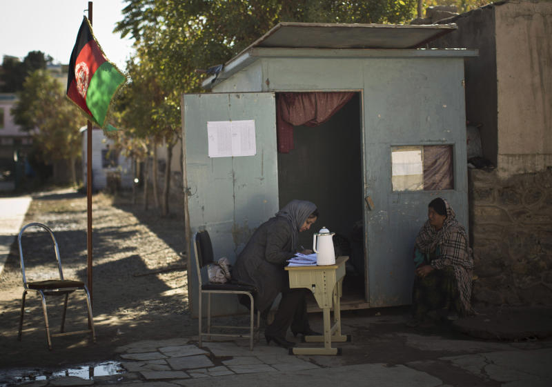 In this Saturday, Nov. 9, 2013 photo, Afghan election workers wait to register voters in a wooden cabin, used as a mobile voter registration place in a school in Kabul, Afghanistan. The Independent Election Commission (IEC) says a bloated voter registration list is a messy start to the 2014 presidential elections, seen as critical to a stable Afghanistan following the final withdrawal of international combat troops at the end of 2014. (AP Photo/Anja Niedringhaus)