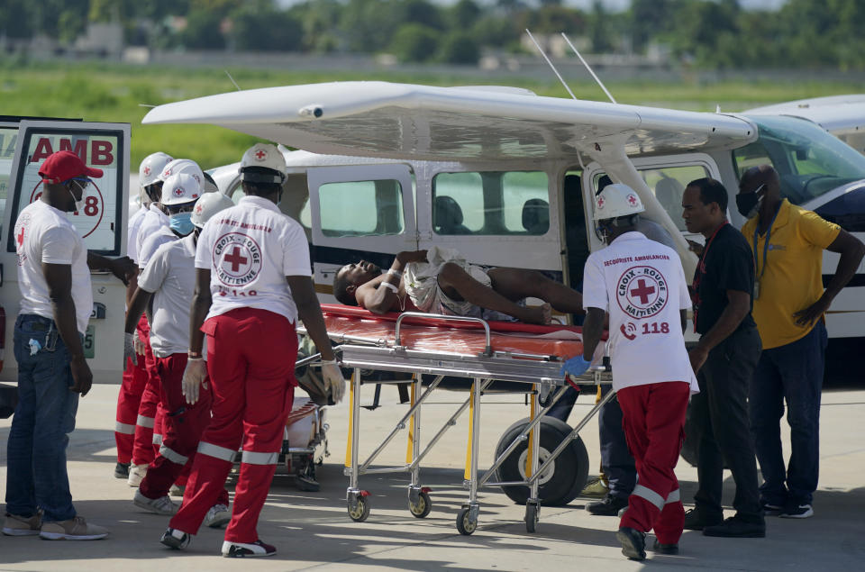 FILE - In this Aug. 15, 2021 file photo, an earthquake victim who was airlifted from the city of Les Cayes, is moved to an ambulance by health workers, at the local terminal of the Toussaint Louverture airport in Port-au-Prince, Haiti. (AP Photo/Fernando Llano, File)