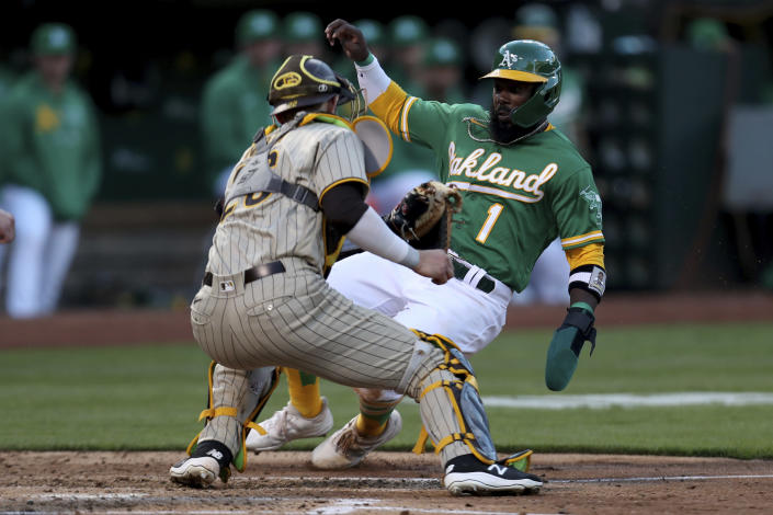 San Diego Padres' Austin Nola, left, tags out Oakland Athletics' Josh Harrison on a double play hit into by Athletics' Mark Canha during the second inning of a baseball game in Oakland, Calif., Tuesday, Aug. 3, 2021. (AP Photo/Jed Jacobsohn)