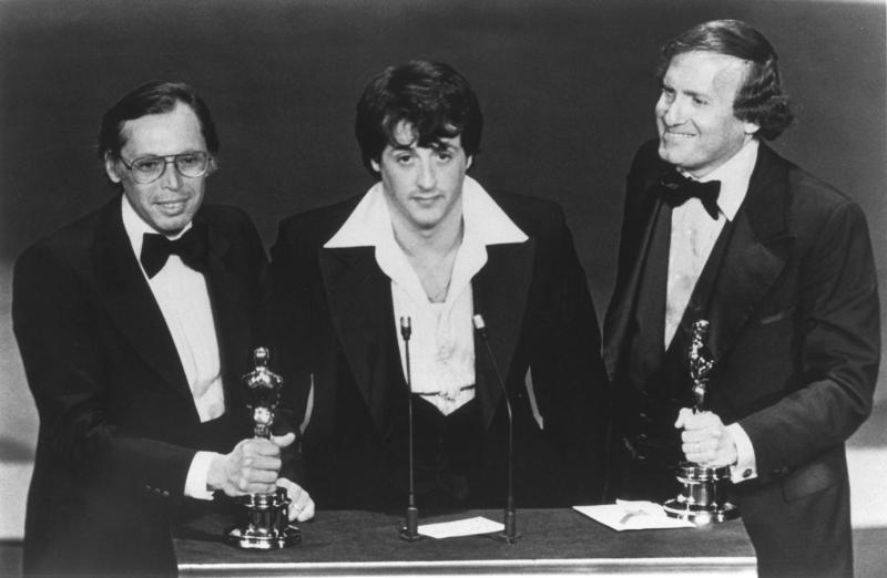 American actor and screenwriter Sylvester Stallone, with producers Irwin Winkler (L), and Robert Chartoff (R), receive the Best Picture award for their movie Rocky during the 49th Academy Awards ceremony. (Photo by Axel Koester/Sygma via Getty Images)