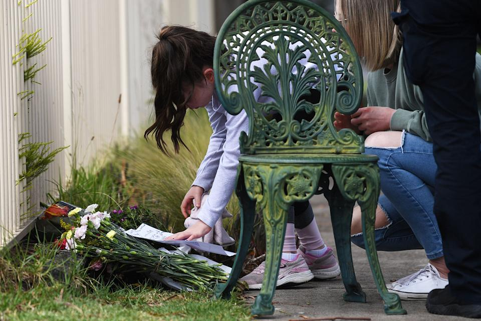 A child leaves a tribute at the makeshift memorial outside the Tullamarine home.