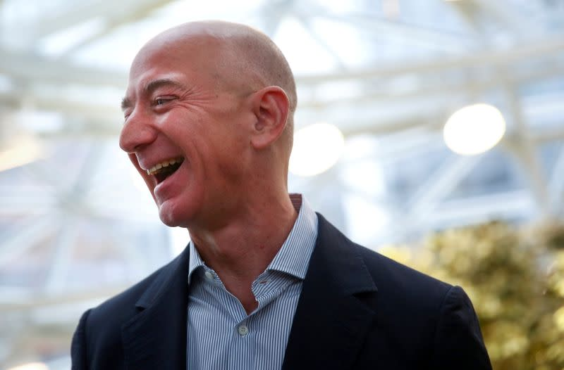 FILE PHOTO: Amazon founder and CEO Jeff Bezos laughs as he talks to the media while touring the new Amazon Spheres during the grand opening in Seattle