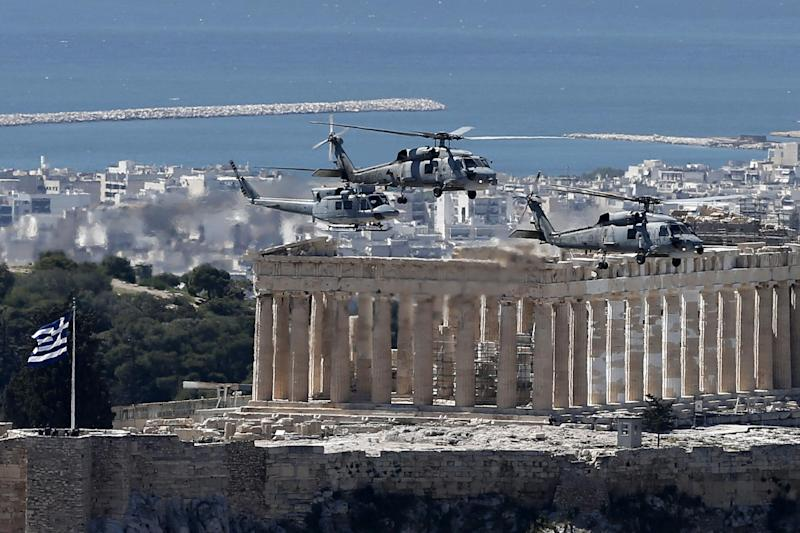 Military helicopters fly over the Parthenon, on the ancient Acropolis hill during a parade in Athens, Tuesday, March 25, 2014, to commemorate Greek Independence Day. The national holiday on March 25 marks the start of Greece's 1821 war of independence against the 400-year Ottoman rule. (AP Photo/ Petros Giannakouris)